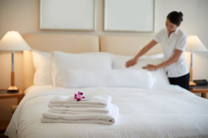 Maid cleaning bedroom after guests, focus of clean towels